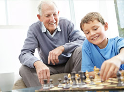 An older man and young boy playing chess